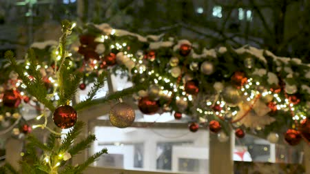 christmas ball gold : Street cafe is beautiful for Christmas. Festive atmosphere in the street. The city is decorated for the holiday. Colored garland Stock Footage