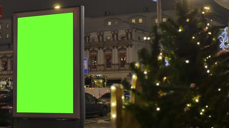 central business district : Billboard with a green screen, located on a busy street. The city is decorated for the new year. Cars move in the evening.