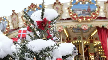 christmas ball gold : Christmas fir tree with toys close-up. Decoration of the city for the holiday. In the background out of focus turns the carousel, on which the children ride. Festive atmosphere.