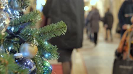 passar : Festive atmosphere in the mall. In the foreground Christmas fir. Not in focus people walk and buy gifts.
