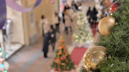 passar : Festive atmosphere in the mall. In the foreground a new year ball. Not in focus people walk and buy gifts.