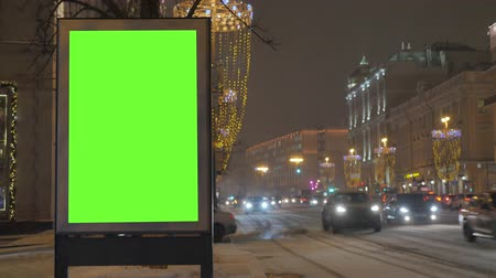 poste de sinalização : A billboard with a green screen on a busy festive street.