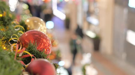 christmas tree decoration : Festive atmosphere in the mall. In the foreground a new year red ball. Not in focus people walk and buy gifts. Stock Footage