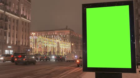 central business district : A big billboard with a green screen on the street decorated for the holiday.