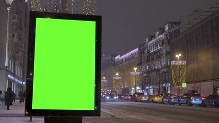 A big billboard with a green screen on the street decorated for the holiday.