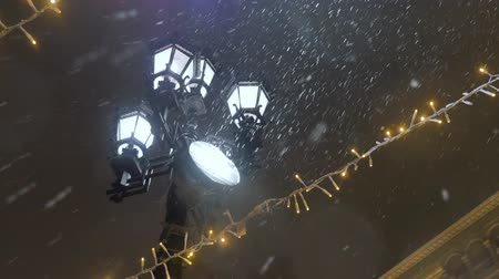 Snowstorm during the New Year holidays. Street lamp shines on snowflakes. Wideo
