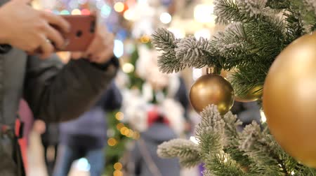 Festive atmosphere in the mall. In the foreground, a Christmas tree with large yellow balls. Out of focus, people go and buy presents. Wideo