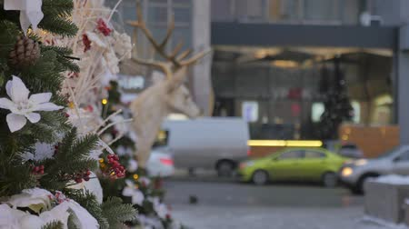 Christmas toys hanging on the tree. In the background, the movement of cars is out of focus. Festive atmosphere.