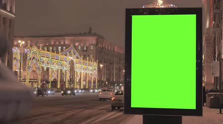 poste de sinalização : A big billboard with a green screen on the street decorated for the holiday.