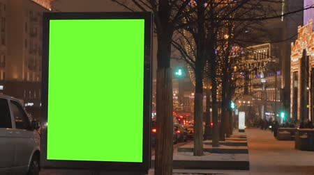 road sign : A big billboard with a green screen on the street decorated for the holiday.