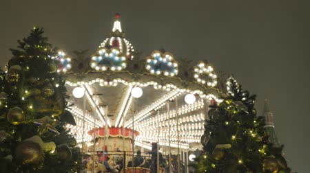Festive atmosphere. People ride on the carousel. In the evening, during a snowfall. Wideo