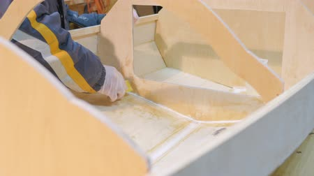 inventor : Male hands closeup. He handles the seams of the boat with epoxy glue for tightness. The boat is made by hand. Stock Footage