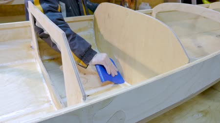 склеивание : Male hands closeup. He handles the seams of the boat with epoxy glue for tightness. The boat is made by hand. Стоковые видеозаписи