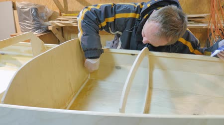 inventor : A man collects a boat made of wood. He is engaged in manual labor.