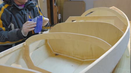 plywood : A man collects a boat made of wood. He is engaged in manual labor.