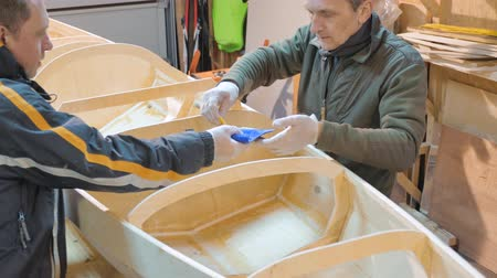 lepení : Two men independently make a boat of wood. They themselves invented the design of the vessel for their travels.
