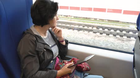 caucasian woman sits train window holds tablet looks out window props her chin Wideo