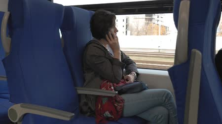 a woman sits on a train talking on the phone side view Wideo
