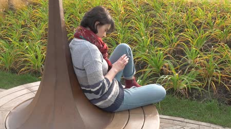 Caucasian woman sits on a round bench, clicks with a phone in her hands