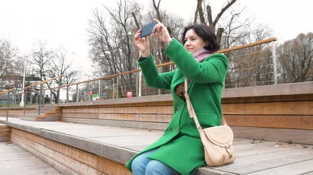 fallen leaves : Caucasian woman sits on podium for spectators in park Takes photo Autumn Stock Footage
