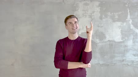 young man stands against a gray wall thoughtful looks left raises his finger up Wideo