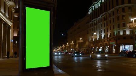City street. Evening. Showcase with a large green screen. Cars are coming. Wideo