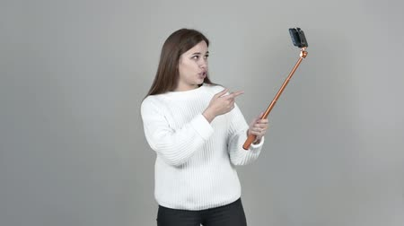 Caucasian girl holds a selfie stick emotionally speaks, gestures, laughs