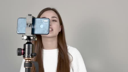 Caucasian girl blogger stands in front of phone camera, makes a video recording