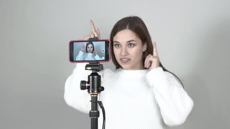 a girl blogger stands in front of a cellphone, says. points up Wideo