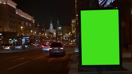 Showcase with a large green screen. Cars are coming. City street. Evening. Wideo