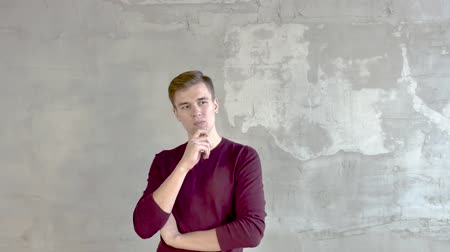 young man stands against a gray wall thoughtful looks right raises his finger up Wideo