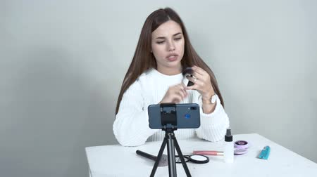 A caucasian girl blogger in front of a cellphone puts a blush on her face brush.