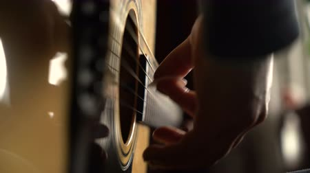 ügyesség : girl plays an acoustic guitar. close-up of strings