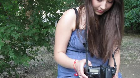 fényképész : Young brunette woman with a DSLR in hands outdoors