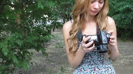 fényképész : Young beautiful woman with a digital camera DSLR in hands