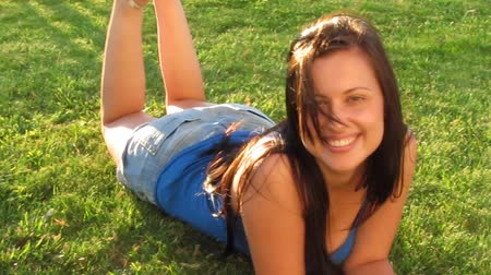 yards : Beautiful Girl lying on the Field.Green Grass. Happy and Smiling