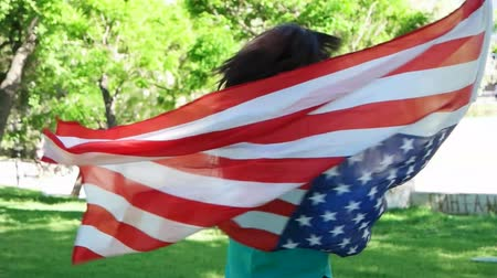 vlastenectví : Patriotic  young woman with the American flag held in her hands dancing slow motion