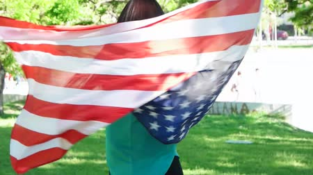 vlastenectví : Happy patriotic  young woman with the American flag held in her hands dancing slowmo video clip