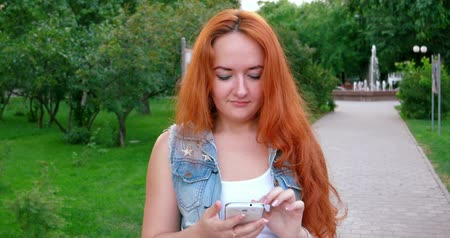 vöröshajú : Redhead Texting on a smartphone. Women with smartphone or phablet outdoors Stock mozgókép