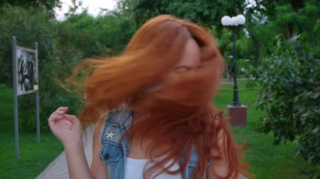 vöröshajú : Young redhead women shaking her head in city park.