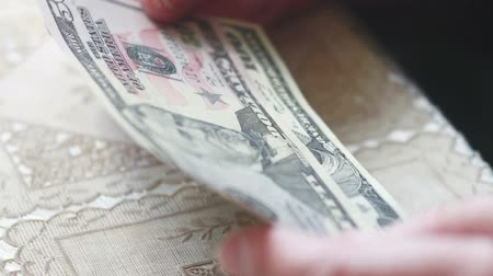 indigence : Closeup of senior lady hands with dollar bills, toned color, selective focus, very shallow DOF
