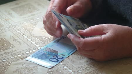 indigence : Aged lady counting euro paper money