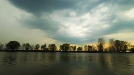 astrakhan : Serene savage scene. A light wind ruffled the water and stormy clouds fly away over the trees on riverbank. Sundown. Stock Footage