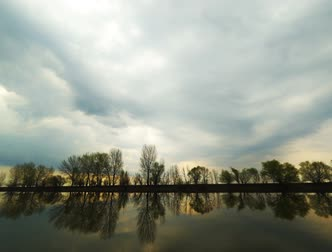 astrakhan : Picturesque view of the river with reflections of the trees on far riverside. Dramatic evening scene under stormy rainy clouds. Rain is startinag and rare drops falling on window. Volga-river near Astrakhan, Russia Stock Footage