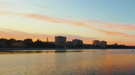 astrakhan : City waterfront timelapse evening time, boats and curlights under orange sunset sky, vintage color