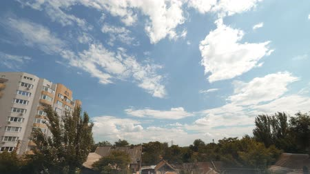 astrakhan : Beautiful day Timelapse. clouds Fly Over Trees, Slum House and Apartment building.
