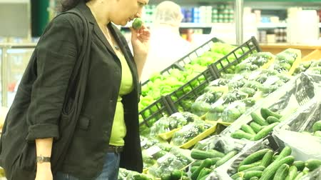 raflar : Astrakhan, Russia, 06 of may 2015: Woman pick cucumber in OKEY hypermarket. Many vegetables on shelves exposed.
