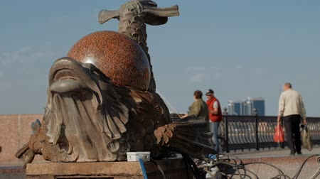 astrakhan : Astrakhan, Russia, April 24, 2018 : Summer scene : Fish-dragon fountain with perl on its back and Volga-river embankment with people in sunny spring day with scyscrapers on background