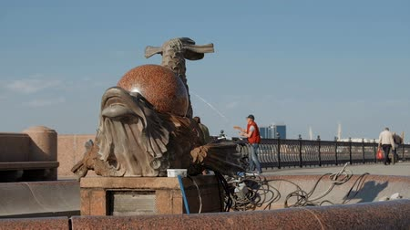 манипуляция : Astrakhan, Russia, April 24, 2018 : Summer scene : Fish-dragon fountain under maintenance with perl on its back and Volga-river embankment with people fishing in sunny spring day with scyscrapers on background