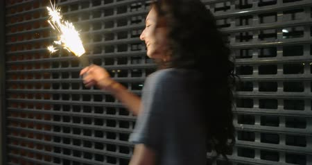 duygusallık : Slowmo footage of teenage girl with sparkler in her hands in front of metal grid fence